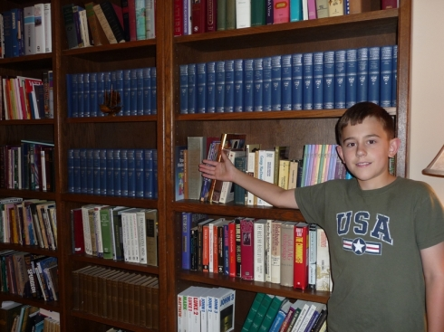 Will points to all the books he plans to read this year, including those blue Harvard Classics, ha!